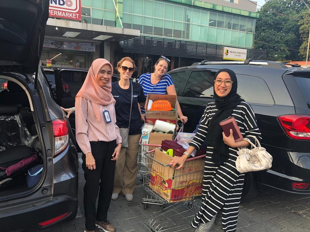 A photo outside of the Super Indo market, showing the store manager, Jayne, Jill, and Lulu with a cart loaded with supplies.