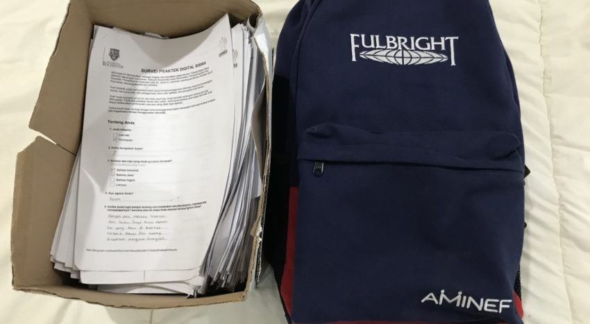 Box of survey responses and backpack full of blank recruiting and data collection copies