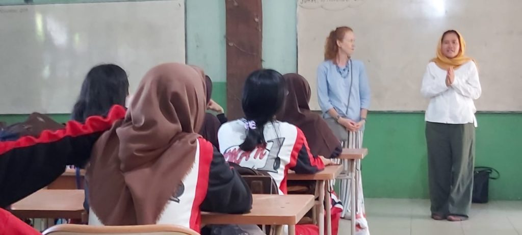 I look on as Puji shares with a high school class